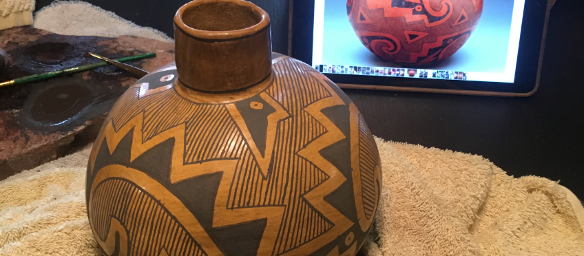 Replica Anasazi pottery being carefully painted using a photo of the original.