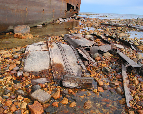 The ship was long ago stripped of its cargo and any valuables, and has been left to gently rust and decay on the tidal flat.