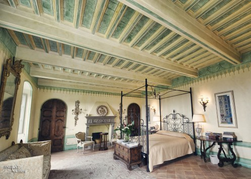 Castello di Santa Eurasia bedroom with a limestone fireplace and wood beams