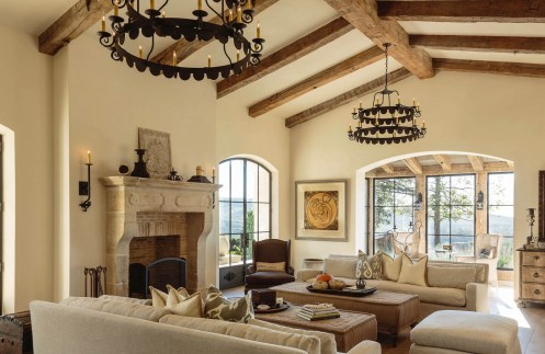 beautiful living room area with limestone fireplace and wood beams