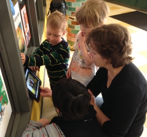 Preprimary children watch a book ad on the iPad with Jane Paha.