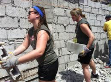 Helping build a house despite the heat and dust