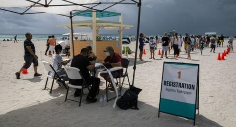 Turistas se vacunan gratis contra el coronavirus en la playa de Miami Beach