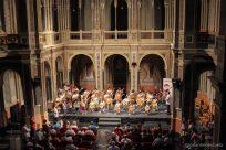 Vista general de todo el salón, con guitarristas en el escenario.
