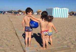 3 niños de espalda en la playa. Uno de ellos lleva una pelota zul bajo el brazo