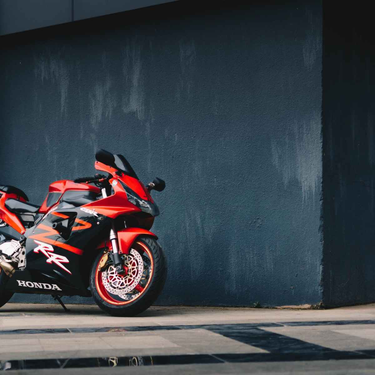 photo of red and black honda sport bike parked next to black wall