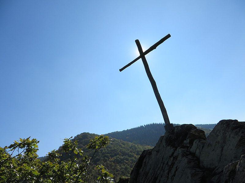 Hier steht ein Bild mit dem Titel: Unbarmherzig brennt die Sonne auf das karges Holzkreuz, das unseren dritten Gipfel markiert (Foto: Hans-Joachim Schneider)