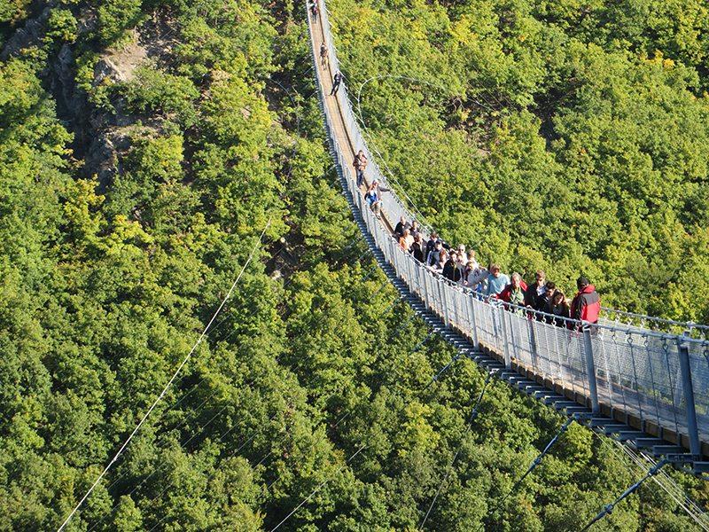 Viele Menschen bewegen sich über die Geierlay Hängebrücke. Unter den vielen, die sich auf die Brücke begeben haben, sind auch ältere und ängstliche Zeitgenossen, dadurch gibt es immer mal wieder Stockungen (Foto: Hans-Joachim Schneider)