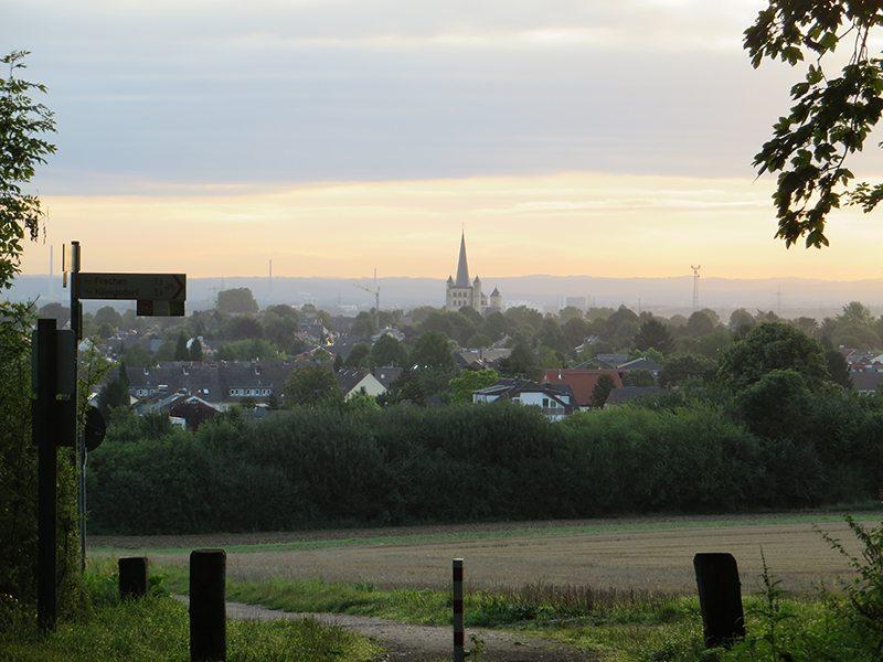 Kleinstadt im Erwachen: Brauweiler mit der mächtigen Nikolaus-Kirche liegt vor dem Wanderer, wenn er aus dem Wald heraustritt (Foto: Hans-Joachim Schneider)