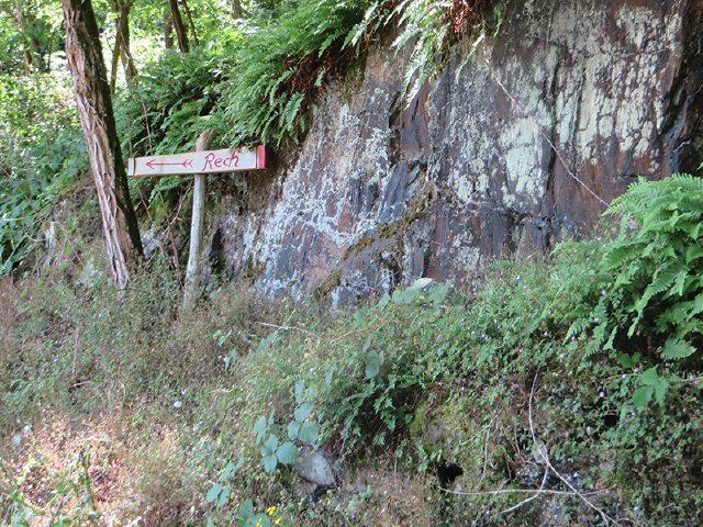 Wegweiser am rechten Rand vor einer Felsmauer weist uns den Weg nach Rech