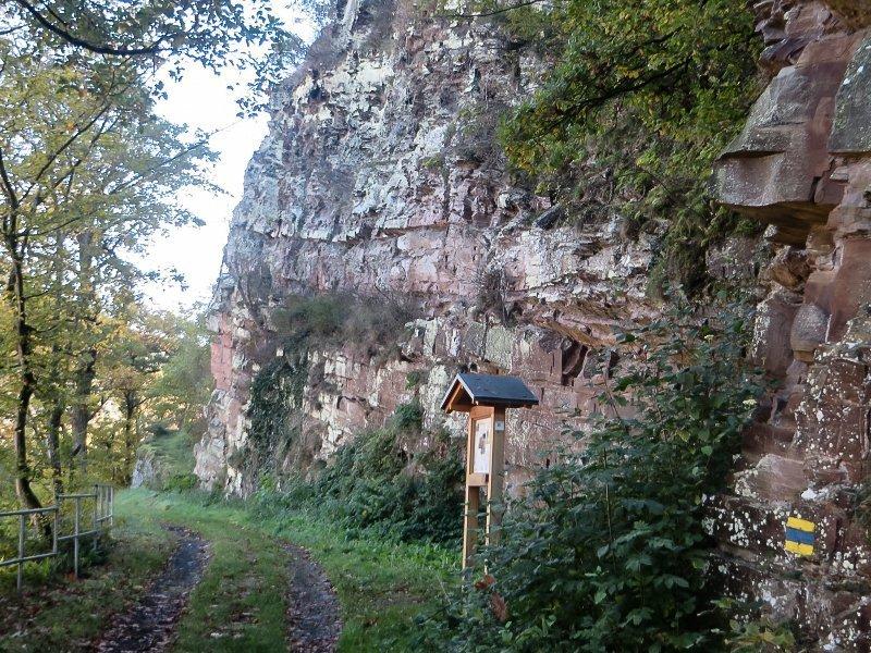 Weg, Felsen, eine senkrechte Felswand, davor eine Infotafel am AhrSteig Blau