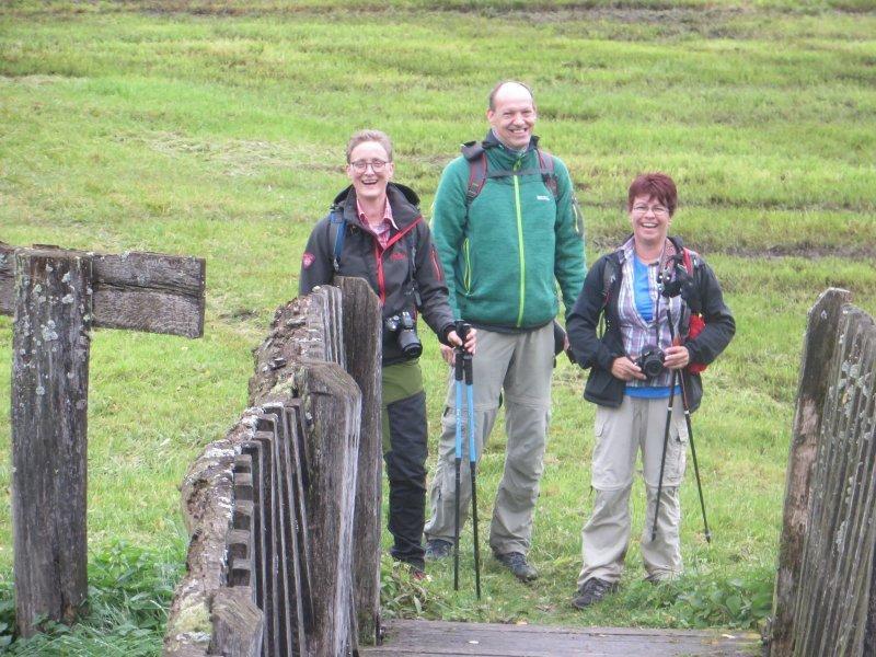 Eine Holzbrücke über einen kleinen Bach. drei Wanderblogger freuen sich.