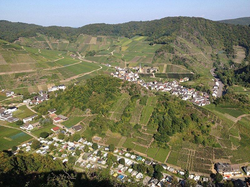 Blick vom Ümerich auf das im Tal liegende Mayschoss, die Häuser verteilen sich um den Weinberg im Zentrum des Ortes