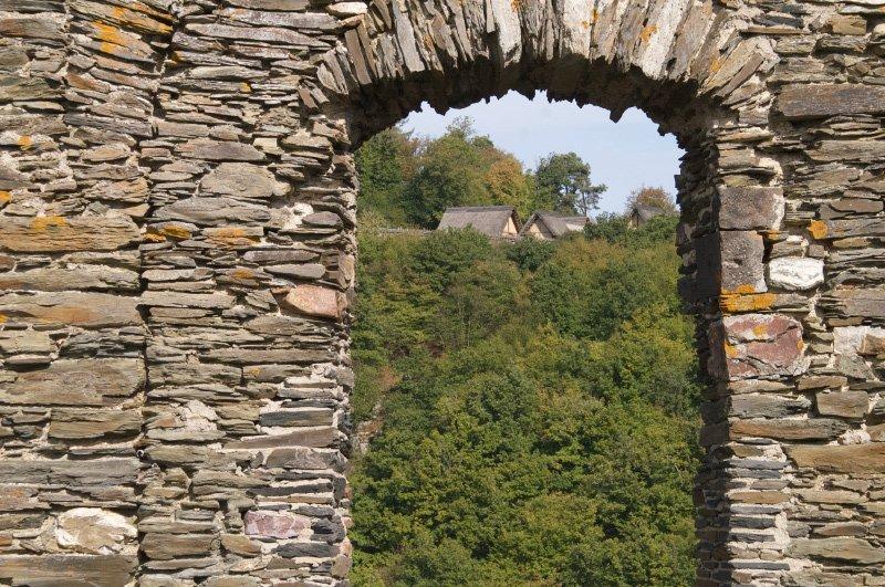 Burgmauern, Fenster, Mauerdurchbruch, und durch das ehemalige Fenster sieht man die Hütten der rekonstruierten Keltensiedlung.
