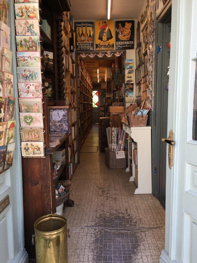 Blick in den Hausflur eines Antiquariats, vom Boden bis zur Decke sind die Regale voller Bücher