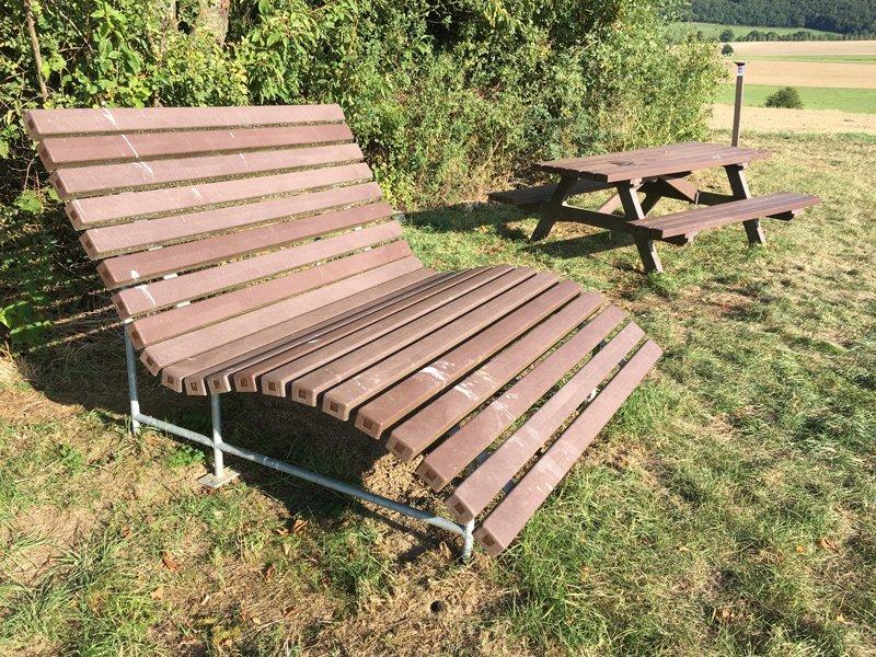Eine große Liege und ein Tisch mit Stühlen, kunststoffüberzogen wir einer Gebüschgruppe