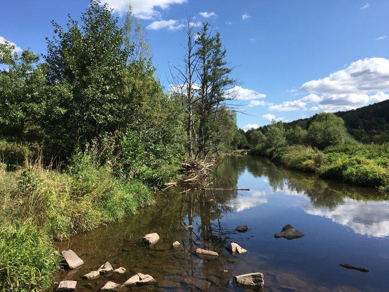 Das Flussbett der ruhig dahinfließenden Nahe, Steine im Wasser, darüber blauer HImmel mit kleinen Wolken