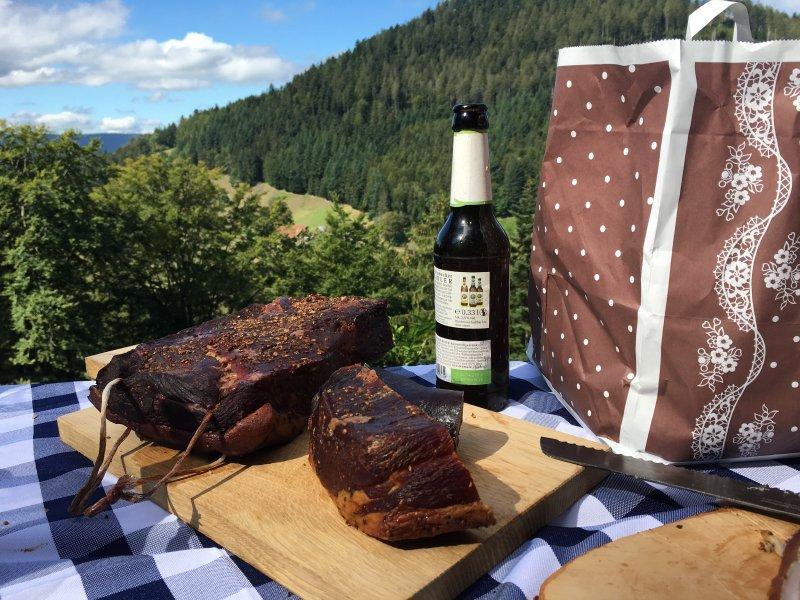 Tisch mit Schinken und Bier, dahinter die grüne Schwarzwald-Szenerie mit Wald und blauem Himmel.