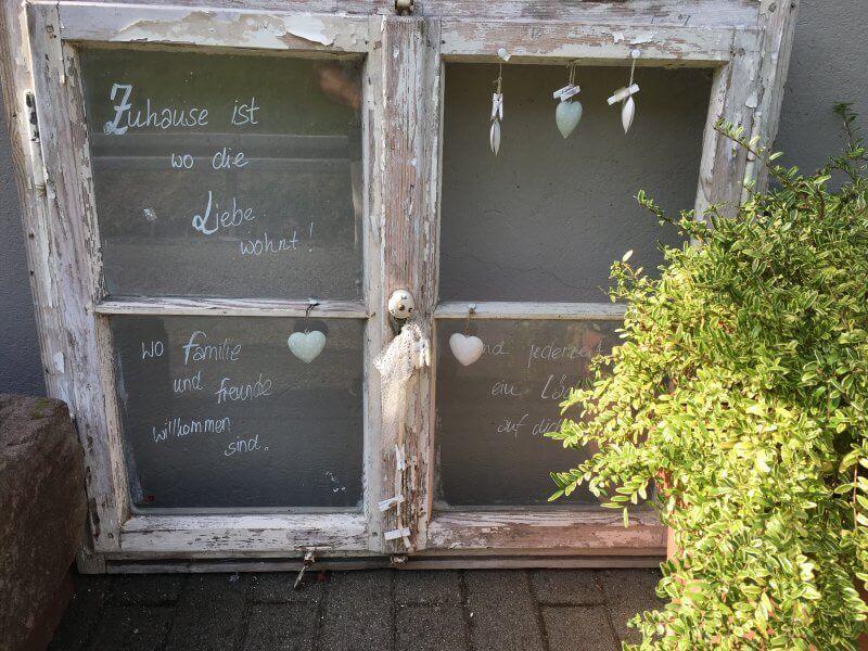 Ein ausgemustertes Fenster liebevoll beschriftet: Zuhause ist, wo die Liebe wohnt