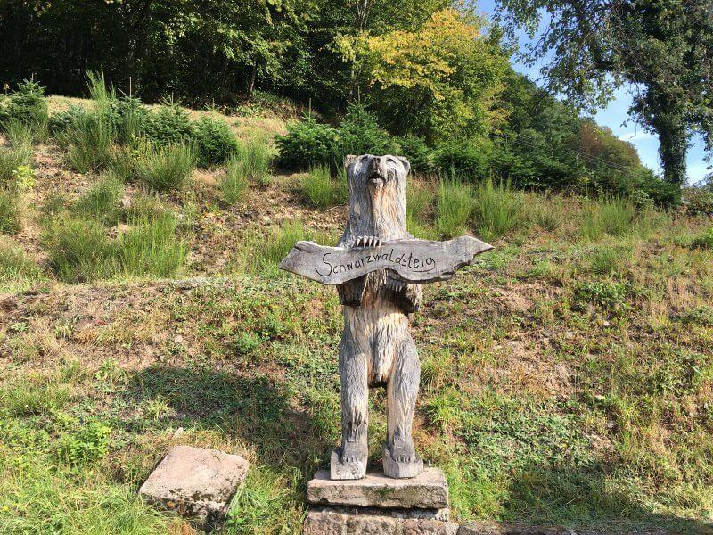 Große aus einem Baumstamm mit der Motorsäge geschnitzte Bärenfigur am Wegrand und viele andere Motive schnitzen unser Holzkünstler