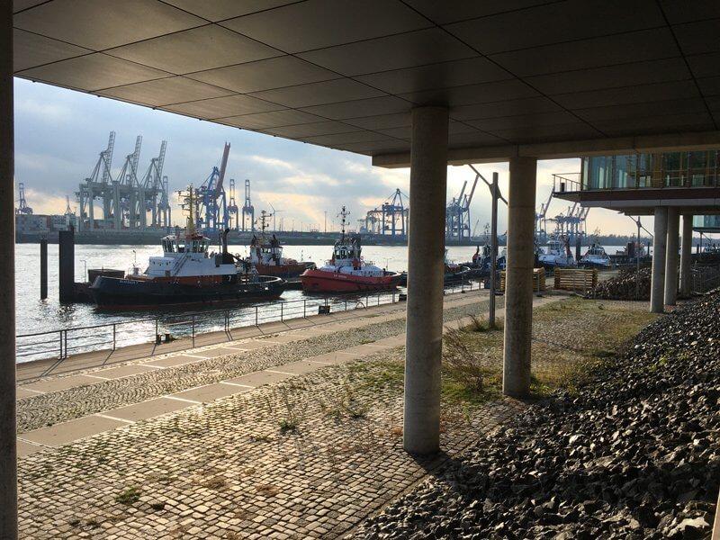 Durch die Säulen gesehen: Schlepper vor der Hafenkulisse