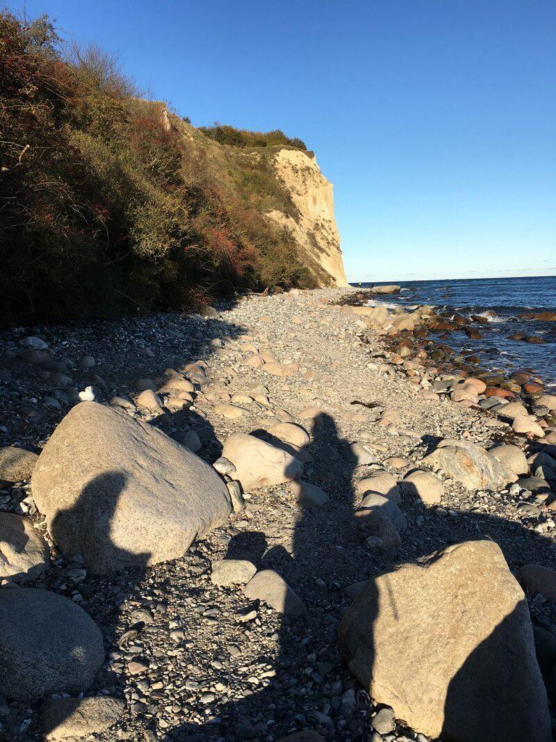 Wanderer auf Rügen, werden beschenkt von der Sonne, hier der Weg am Strand entliang nach Vitt, im Hintergrund die Klippe unterhalb der alten Slawenburg.