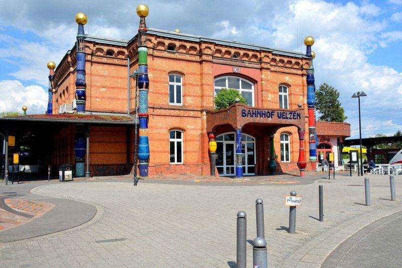 Rötliches Bahnhofsgebäude mit bunten Verzierungen, gestaltet von Friedensreich Hundertwasser