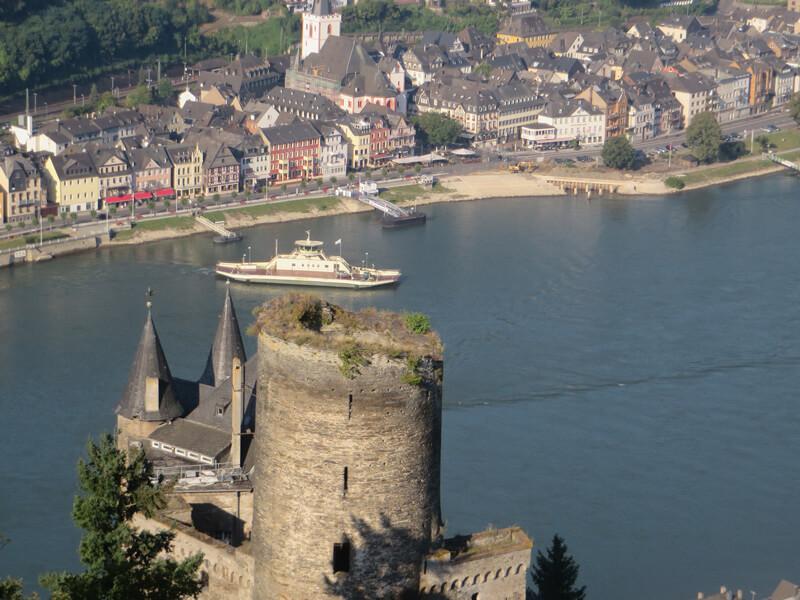 Im Vordergrund ein alter Burgturm, dahinter sieht man einen breiten Fluss, eine Fähre auf dem Wasser und am gegenüberliegenden Ufer die Häuser der Ortschaft St. Goar. Die ganze Szenerie ist in Sonnenlicht eingetaucht.