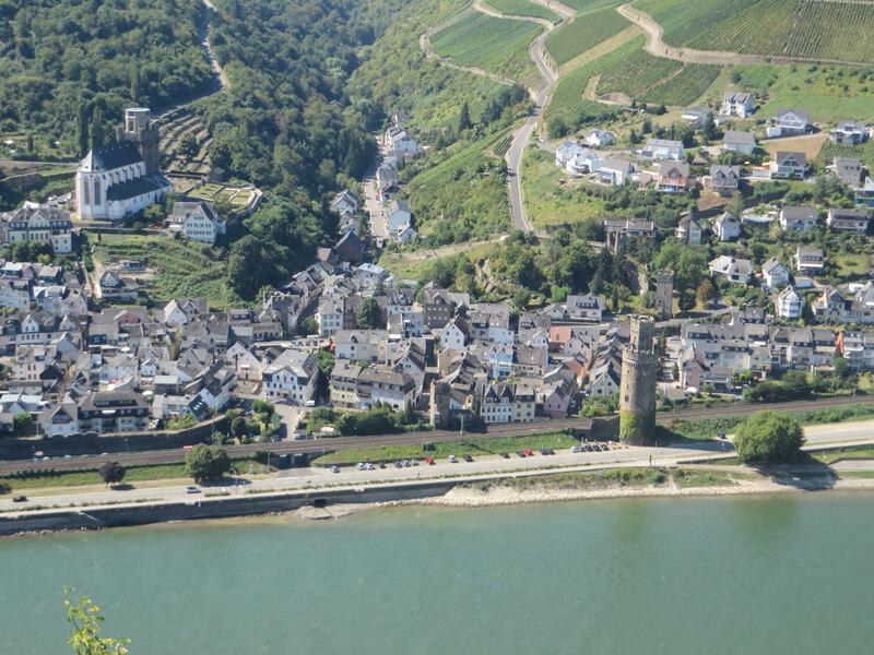 Blick von oben auf den breiten Fluss, am gegenüberliegenden Ufer die zahlreichen Gebäude eines Ortes. Direkt am Flussufer ein alter leicht schiefer Turm.
