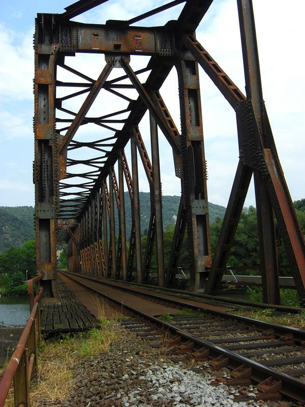 Das rostige Eisengerüst eines alten Bahnviadukts rahmt eine eingleisige Bahnstrecke ein.