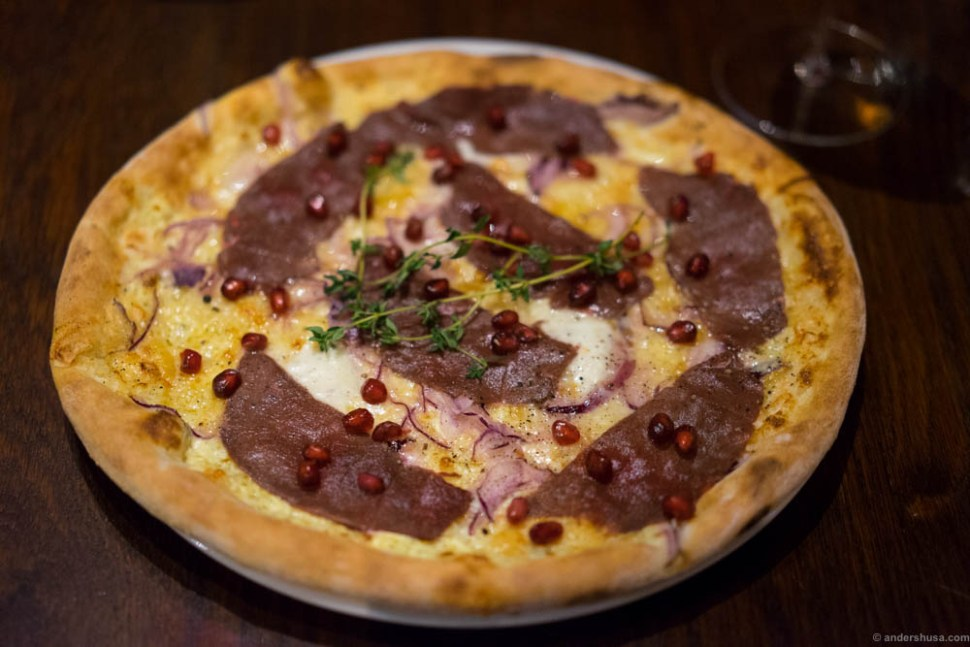 White pizza with carpaccio of reeindeer from Røros, with pomegranate and red onion.