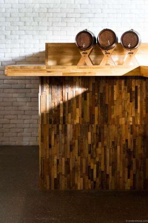 The bar counter made of driftwood. Barrels for aquavit