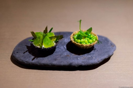 Mini tartlets. On the right: sweet peas & sugar snap in lovage oil, ricotta and candied yuzu in a roasted kombu tart shell. On the left: kiwi puree, pickled green tomatoes, sea asparagus, creme fraiche and fried nori in a soy tart shell.