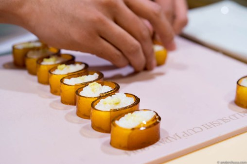 Carefully wrapping each piece of rice in kombu gel rather than nori