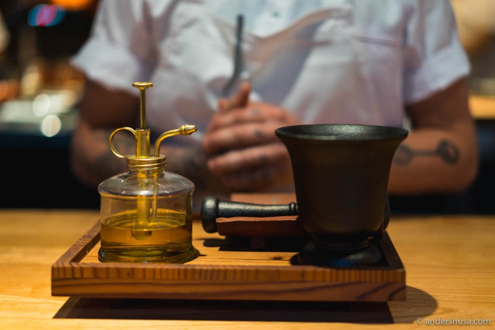 Cold-pressed rapeseed oil and a mortar & pestle with herbs inside
