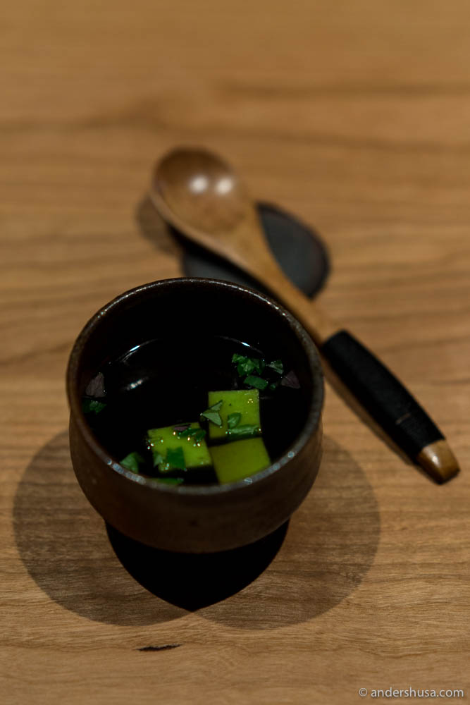 Broth of the duck and fermented chanterelle juice, with tofu of peas and fresh herbs