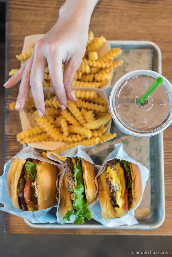 ShackBurgers with a side of crinkle cut fries, and a milkshake.