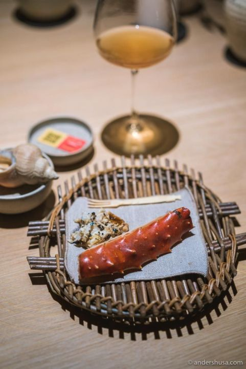 """Barbecued king crab """"collar"""" with a black truffle sauce in the back."""
