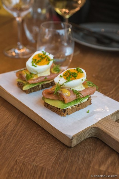 Smoked salmon smørrebrød with avocado, boiled eggs, dill, and mustard.