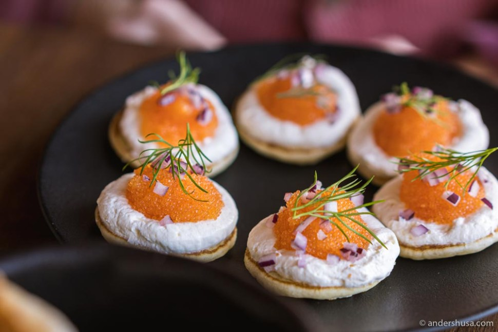 Blinis topped with sour cream, løyrom, dill, and red onions.