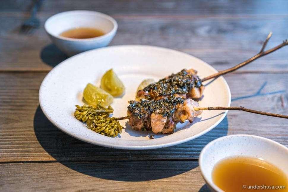 "Chicken skewers from leg heart and lardo, covered in garlic, gooseberry & chili ""kosho."""