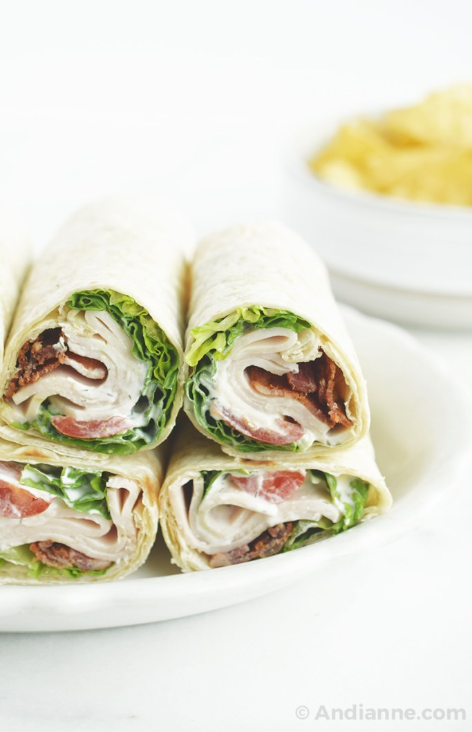 chicken bacon ranch wraps rolled and stacked on a plate with tortilla chips in background