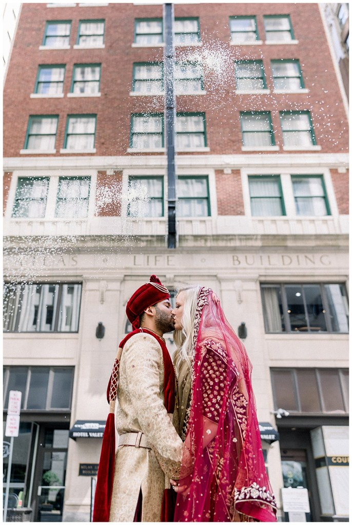 Bride and groom kiss in front of downtown building with snow falling| Hindu wedding Tulsa| Indian wedding Tulsa| Sky Loft at First Place Tower| Tulsa wedding photographer| Andi Bravo Photography