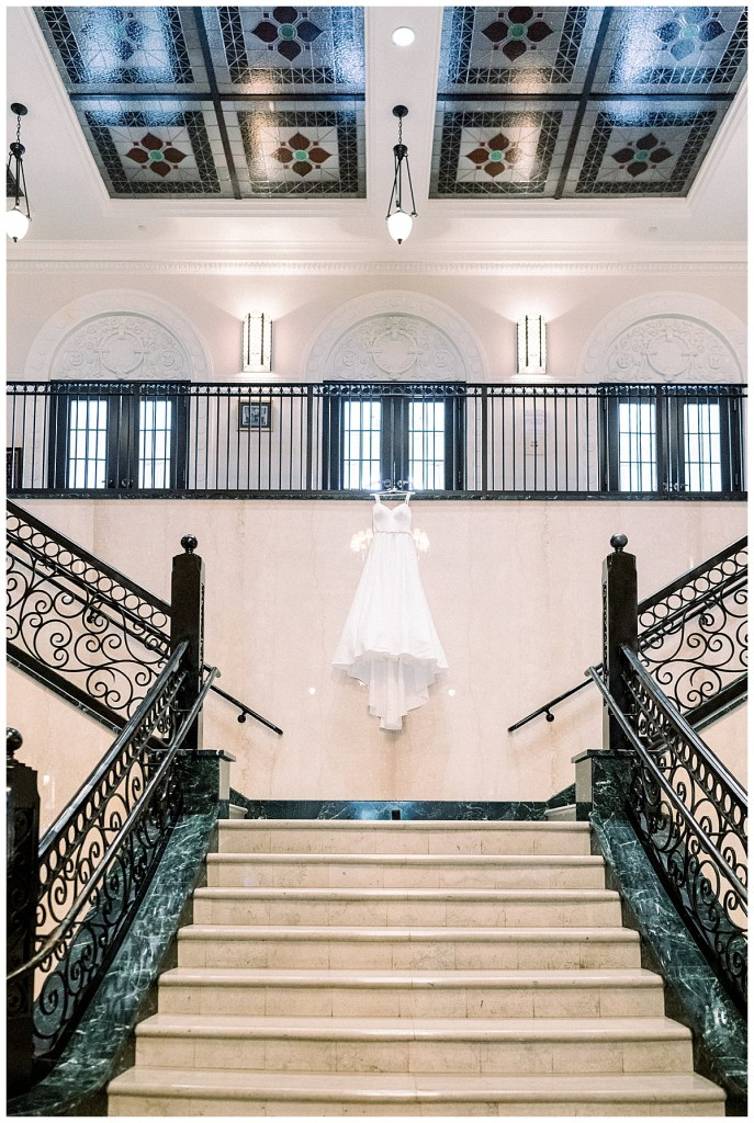 Wedding gown hanging from railing in front of staircase at The Mayo Hotel Tulsa| Tulsa wedding photographer| Destination wedding photographer| Andi Bravo Photography
