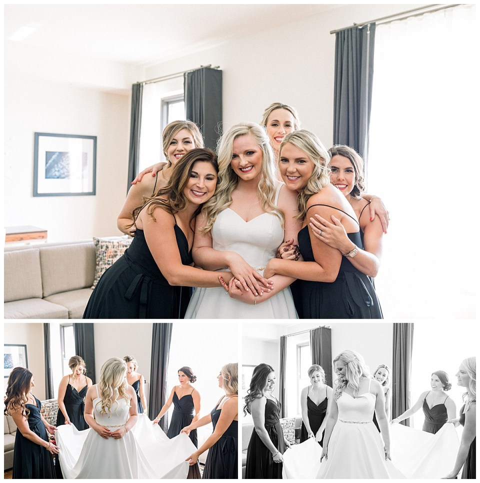 Bridesmaids hold bride's dress train around her and come in for a hug| The Mayo Hotel| Tulsa Wedding| Andi Bravo Photography
