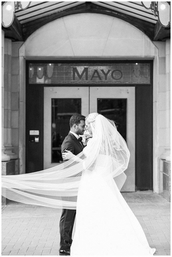 Black and white of bride and groom standing outside of The Mayo Hotel| Veil sweeping around them while they nuzzle| Tulsa wedding| Tulsa wedding photographer| Destination wedding photographer| Andi Bravo Photography