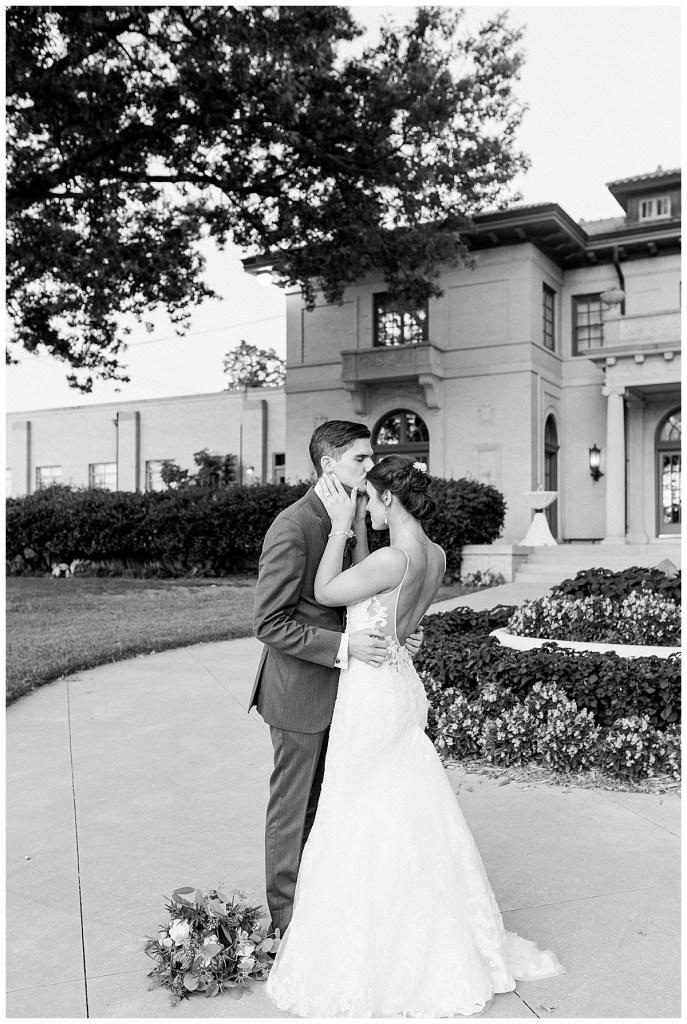 Black and white of groom kissing bride on forehead outside wedding venue| The Mansion at Woodward Park| Andi Bravo Photography
