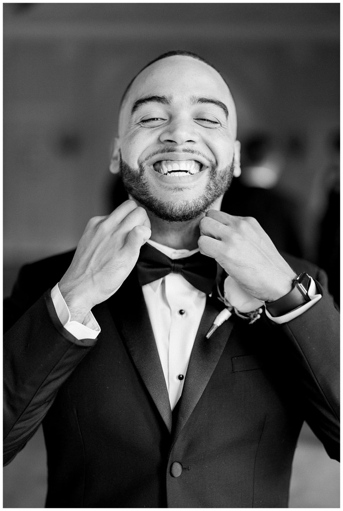 Black and white photo of groom grinning big while adjusting bowtie| happy groom| Tulsa wedding| Andi Bravo Photography