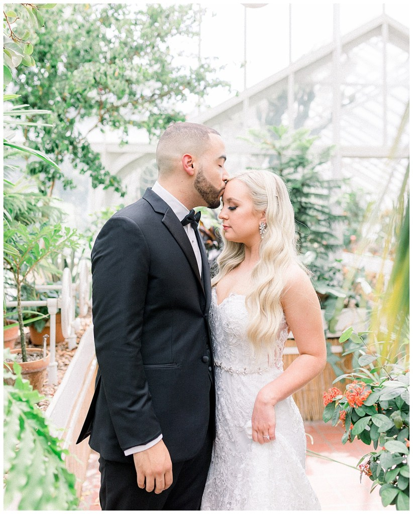 Groom kisses bride on forehead in greenhouse| forehead kiss| Wedding first look| Tulsa wedding venue| Andi Bravo Photography