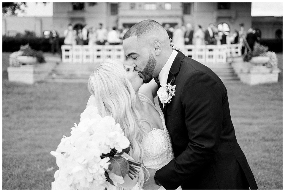 Black and white shot of bride and groom kissing after wedding ceremony with Mansion at Woodward Park in the background| Tulsa wedding ceremony| Andi Bravo Photography